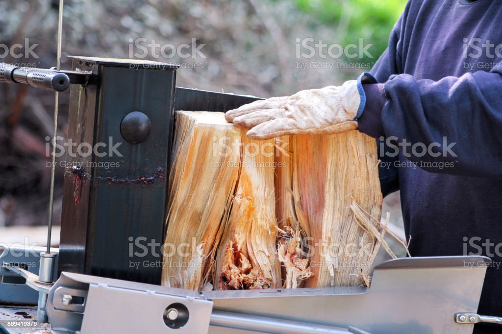 Viu o corte da madeira para o inverno. Vi um lenha de corte do homem para o inverno usando uma madeira máquina moderna. Indústria da madeira. Estação de aquecimento, temporada de inverno. Recurso renovável de energia. Conceito ambiental. - foto de acervo