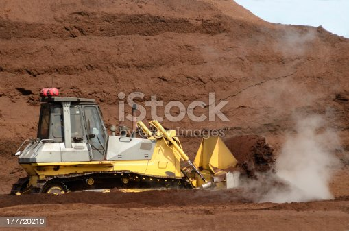 Small bulldozer working a pile of decomposing sawdust that is used for fertilizer