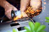Man using a electric saw, sparks flying.
