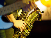 Playing saxophone, blurred guitar in the foreground