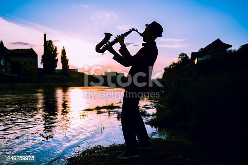 Silhouette of a man playing saxophone on the river at sunset