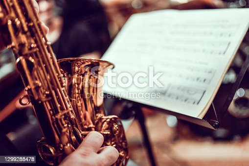 istock Sax Player Reading Sheet Music 1299288478