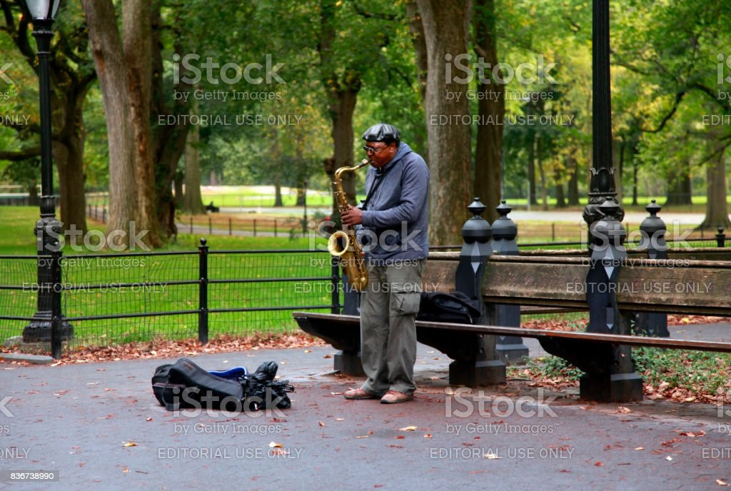 A saxaphonist busking in Central Park's Bethesda Terrace, a popular tourist attraction stock photo