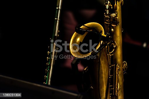 Saxophone and flute, stage close up in low key, black isolated