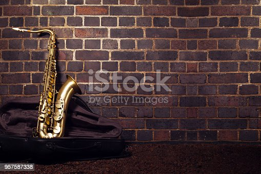 Saxophone leaning against a red brick wall