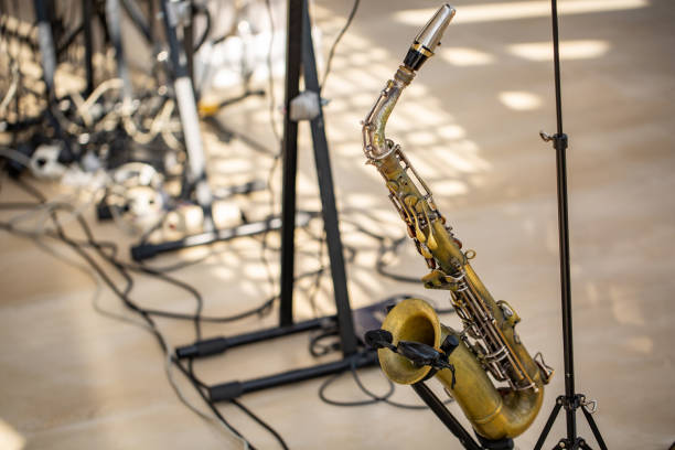 saxophone of golden color stands on the rack on the stage stock photo