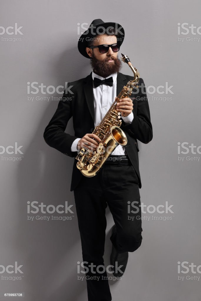 Saxophone player leaning against a wall stock photo
