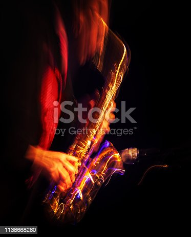 Jazz music concept. Saxophone player performing on stage. Sax player going crazy. Abstract motion blurred image.