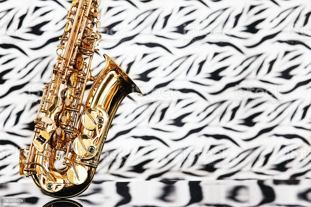 Saxophone rests on out-of-focus patterned velvet royalty-free stock photo