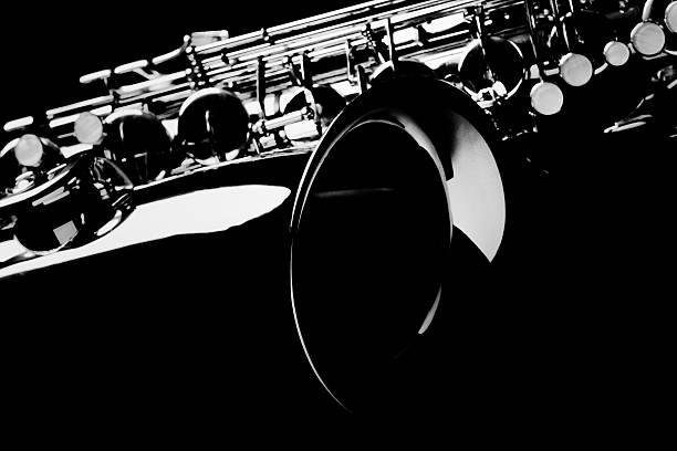 saxophon mit schwarzem hintergrund. - altsaxophon stock-fotos und bilder