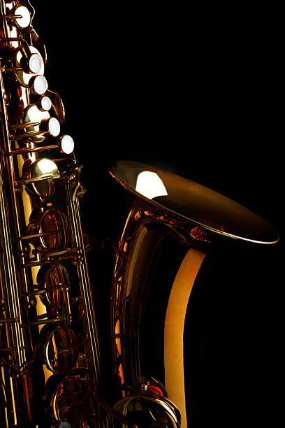 saxophon mit schwarzem hintergrund - altsaxophon stock-fotos und bilder