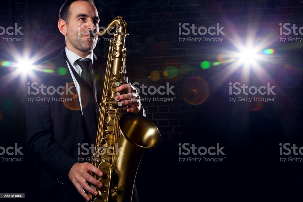 Saxophonist playing with passion at club stock photo