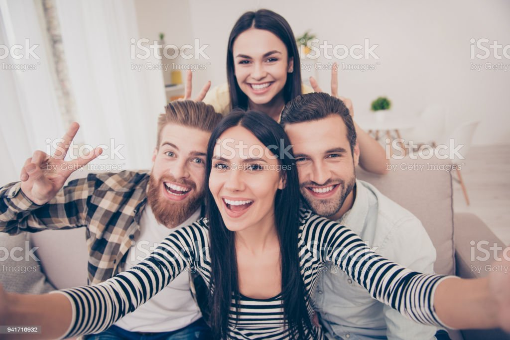 Say Cheese! Close up of an excited friend`s selfie, taken at home. Young people enjoy their company, smiling and showing two fingers sign stock photo