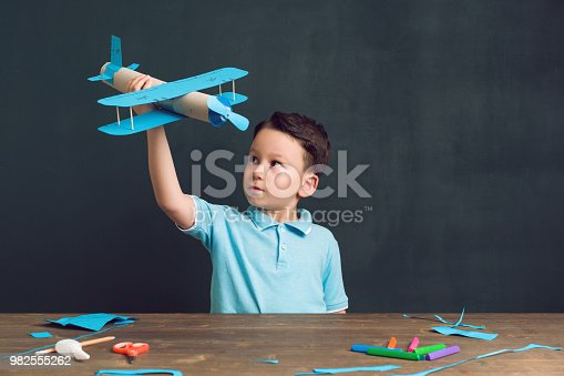 The child making a plane. He used cardboard and paper. This is an innovation for his. He is a successful student at the age of 4-5.