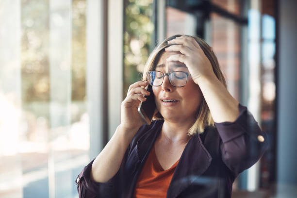 Say it isn't so! Shot of a young woman looking distraught while talking on a mobile phone in a modern office woman crying stock pictures, royalty-free photos & images