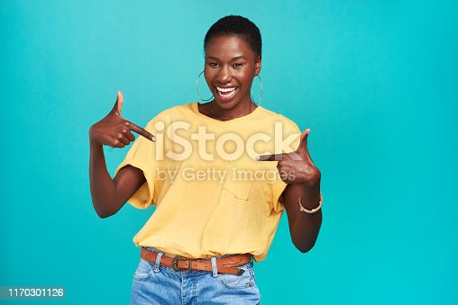Studio shot of a confident young woman pointing at her t shirt against a turquoise background