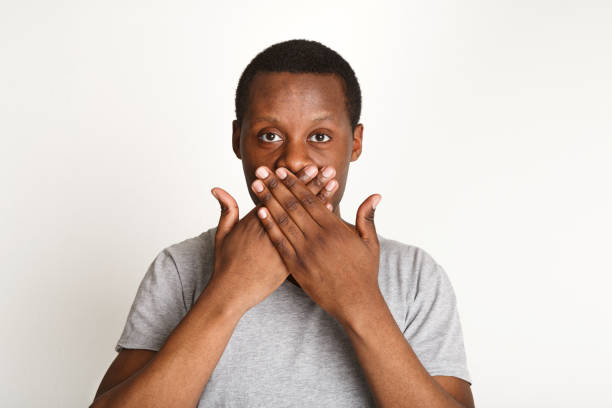 Say nothing concept, black man covering mouth with hand stock photo