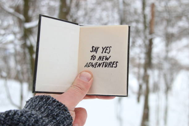 say yes to new adventures. hand holding a book with - neue abenteuer stock-fotos und bilder
