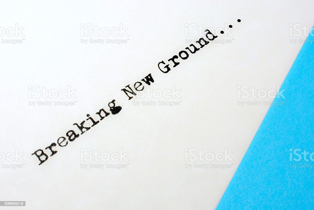 Saying- Breaking New Ground- with blue and white color stock photo