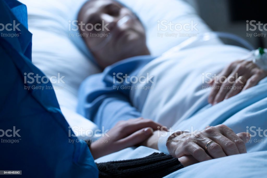 Saying goodbye to dying mother Young woman holding hands and saying goodbye to her dying of cancer mother in hospice Adult Stock Photo