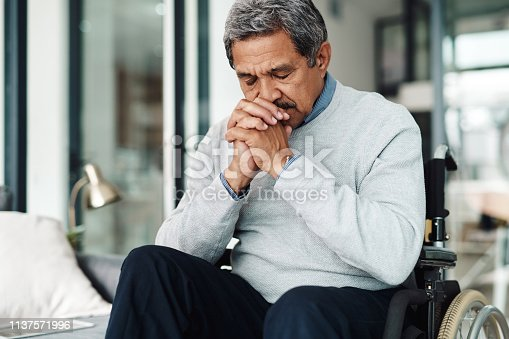 Shot of a relaxed elderly man seated in a wheelchair while praying at home during the day