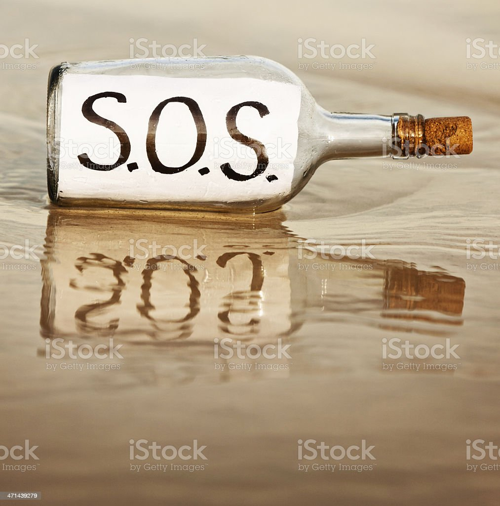 SOS says desperate message in bottle at waters edge royalty-free stock photo