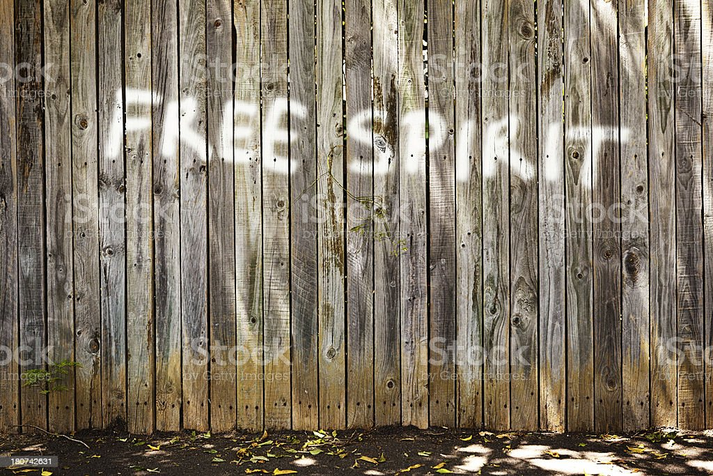 FREE SPIRIT says grafffiti on old wooden fence, hippies rule! royalty-free stock photo