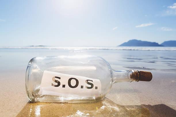 s.o.s. sagt nachricht in der flasche am strand fehlgeschlagen - rettungsinsel stock-fotos und bilder