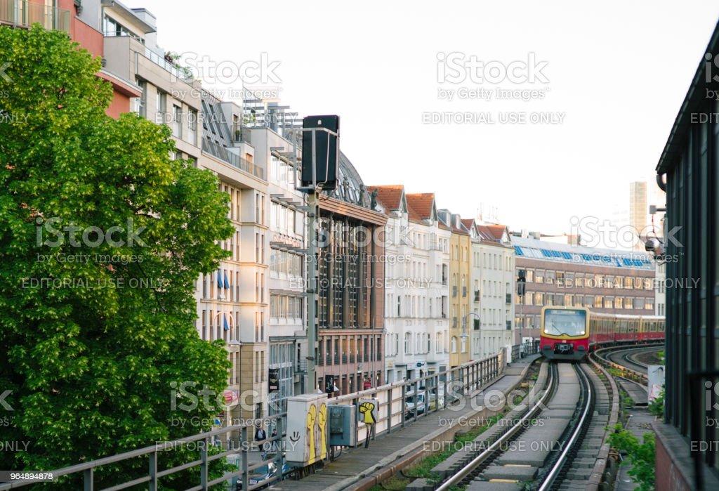 在車站的柏林的房子之間的鐵軌上的火車列車。 - 免版稅公共交通系統圖庫照片