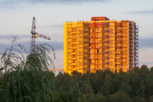 scaffold covered apartment building with construction crane, evening sunset shot scaffold covered apartment building with construction crane, evening sunset shot apparently stock pictures, royalty-free photos & images