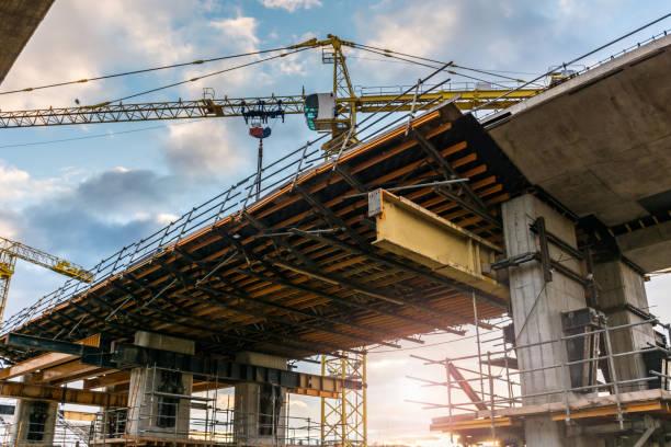 impalcature e gru nella costruzione di un ponte per un'autostrada - intelaiatura foto e immagini stock