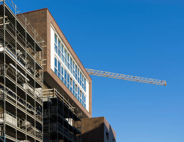 scaffolding housing construction with tower crane - foto stock