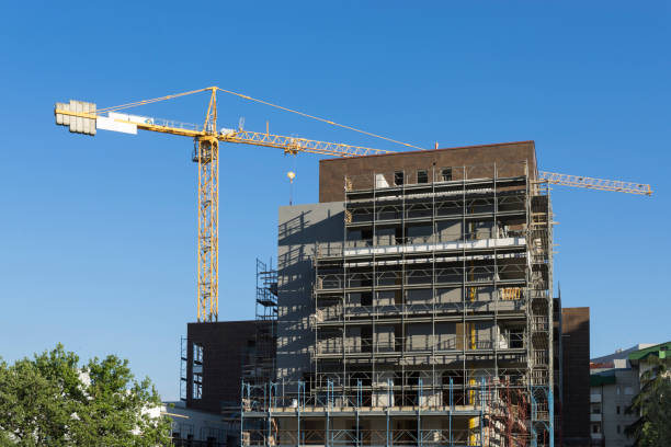 scaffolding housing construction with yellow tower crane - foto stock
