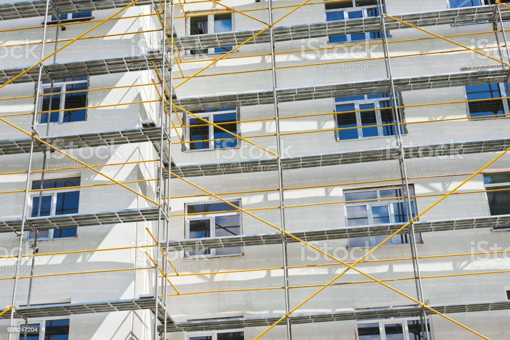 scaffolding near a new house under construction, white wall and window, yellow pipe stock photo