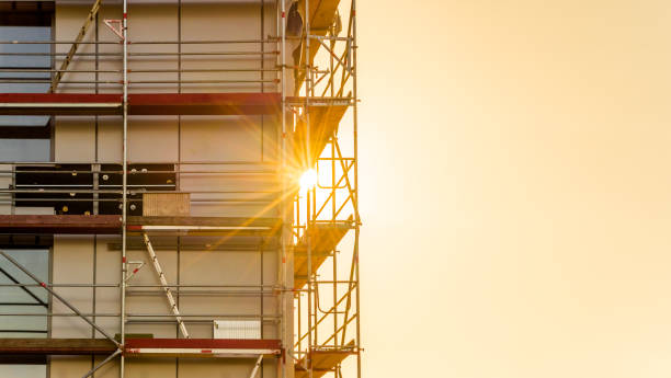 Gerüst auf einer Baustelle. Geschäftshaus mit Sonnenstrahlen im Gegenlicht – Foto