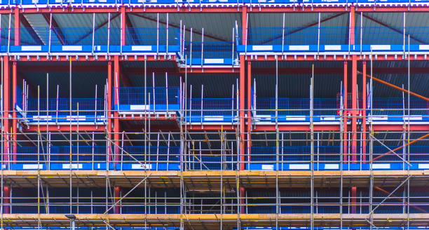 Scaffolding wall. Construction workers working on scaffolding with safety net. Background of construction wall on site. Building Construction. New house development under construction. Safety scaffold stock photo