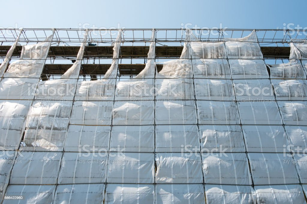 scaffolding with white canvas and blue sky background stock photo