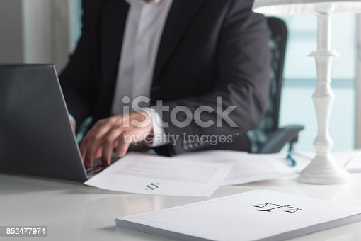 istock Scale and justice sign on pile of paper. Lawyer working in office. Attorney writing a legal document with laptop computer. Law firm and business concept. 852477974