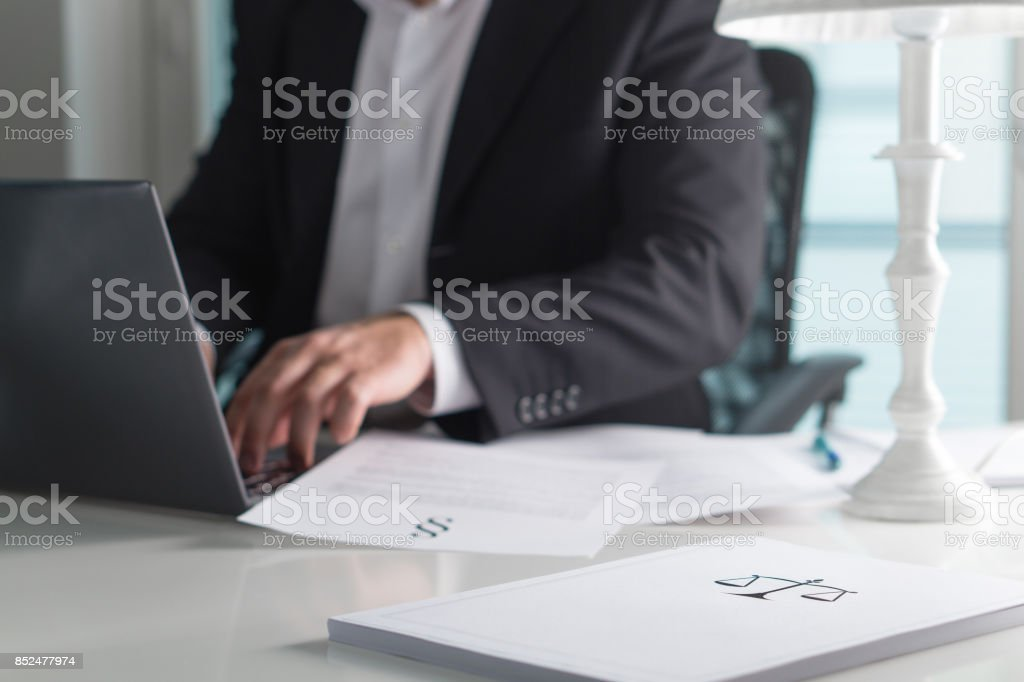 Scale and justice sign on pile of paper. Lawyer working in office. Attorney writing a legal document with laptop computer. Law firm and business concept. stock photo