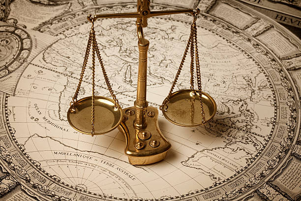 Scale of justice on ancient map stock photo