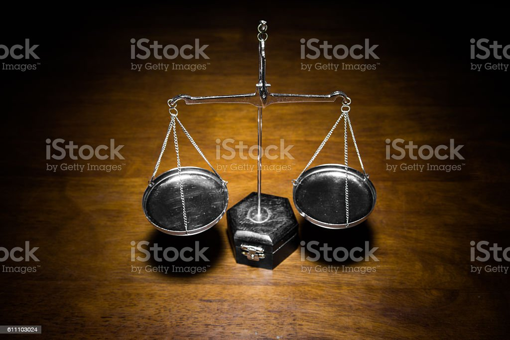 Scale of justice on wooden table stock photo