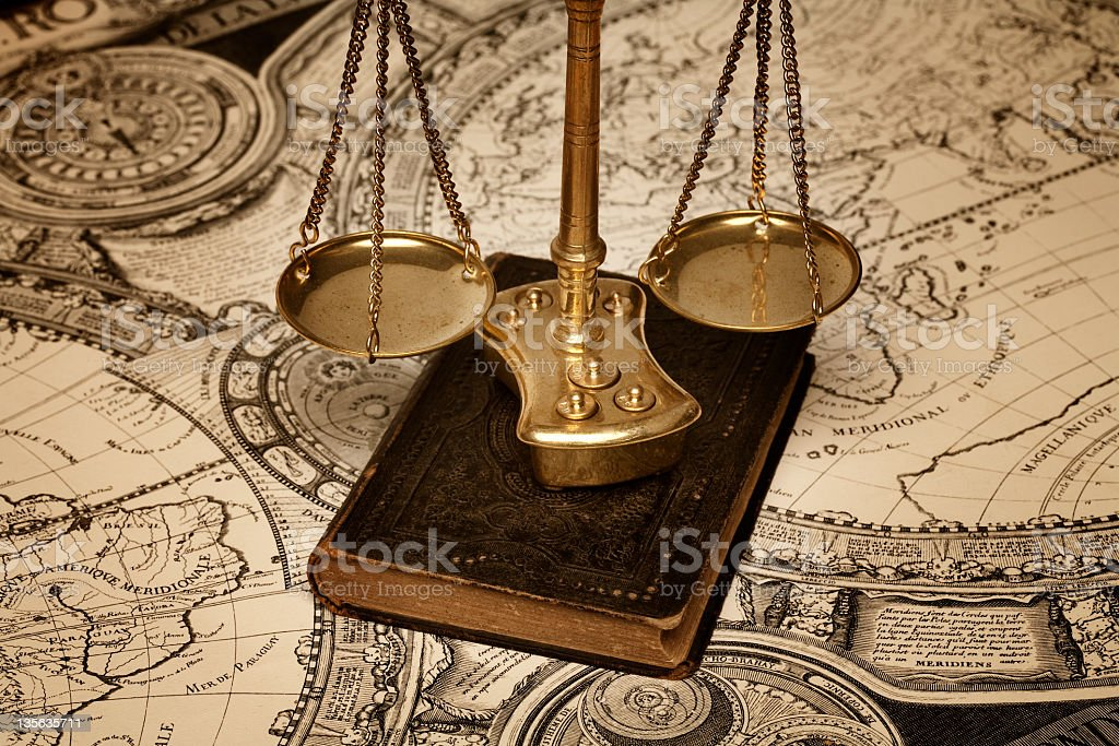 Scale of justice over old book and ancient map Golden justice scale on top of leather book and ancient world map Ancient Stock Photo