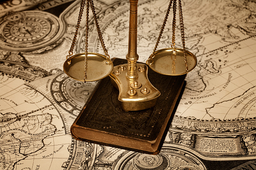 Scale Of Justice Over Old Book And Ancient Map Stock Photo - Download Image Now
