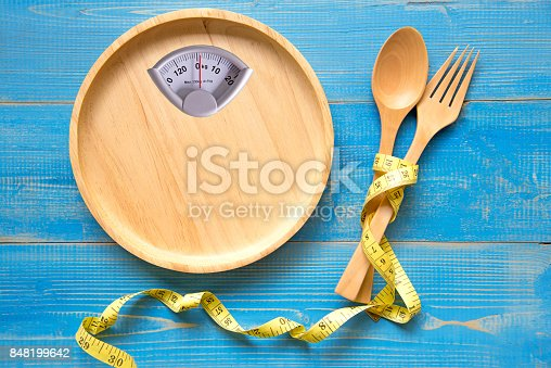 Scale shaped on the wood plate with a fork and spoon, blue background.  Diet and Healthy Concept