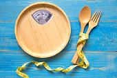 木の皿にフォークとスプーン、青色の背景色と形のスケール。 ダイエットと健康の概念