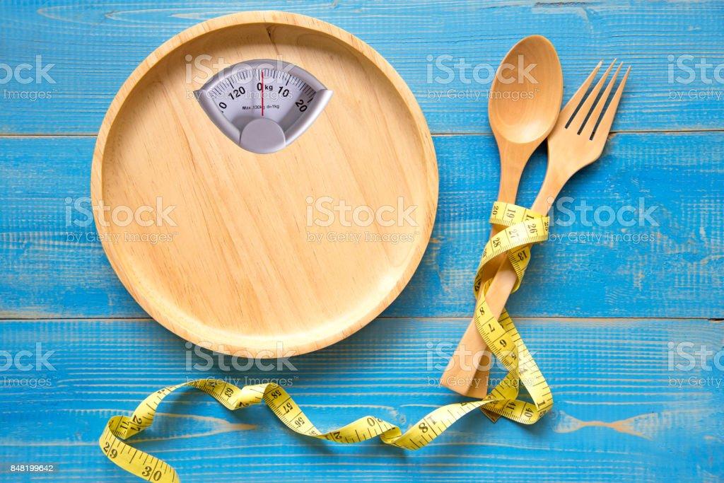 Escala en forma de la placa de madera con un tenedor y cuchara, y fondo azul.  Dieta y el concepto saludable - foto de stock