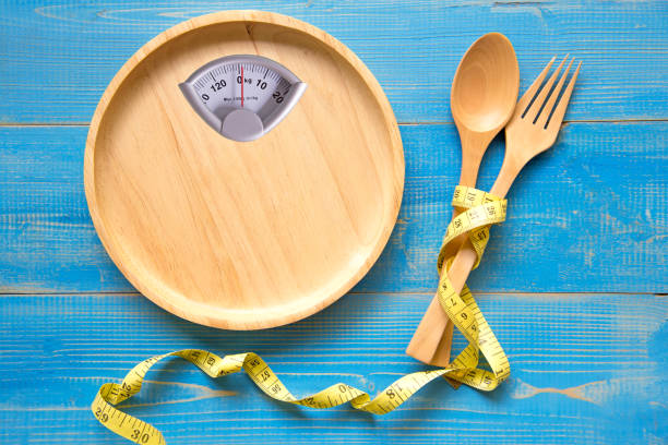 scale shaped on the wood plate with a fork and spoon, blue background.  diet and healthy concept - dieting stock pictures, royalty-free photos & images