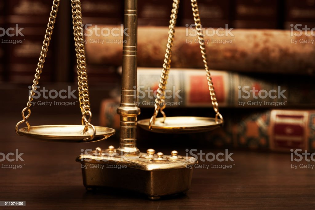 A Scale surrounded by old books. Justice concept stock photo