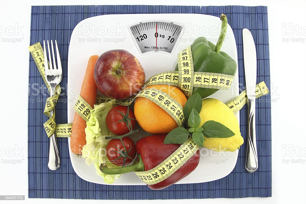 Scale with fruits and vegetables on top with measuring tape stock photo