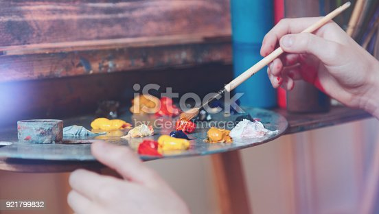 624112404istockphoto Scaled up shot of hand of child mixing colorful paints 921799832